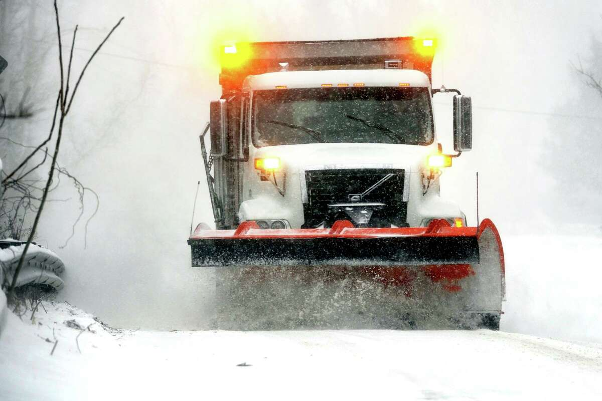A department of public works truck plows snow along James Farm Rd., in Stratford, Conn. Feb. 1, 2021.
