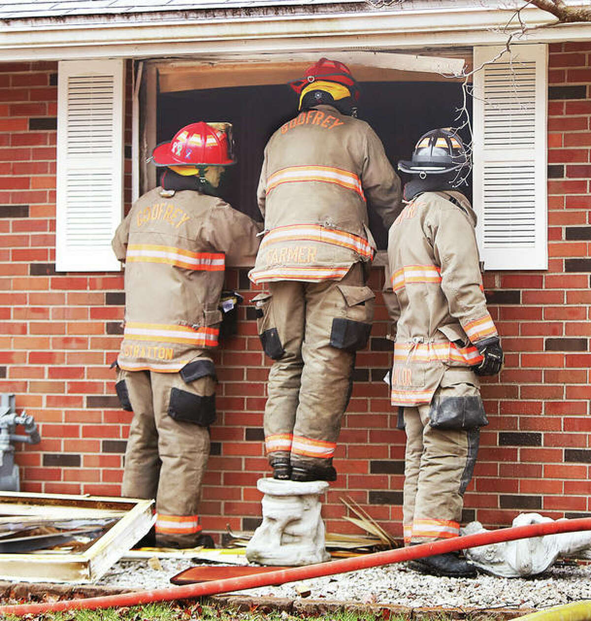 Godfrey firefighters stand and stare through a broken out window into a house Monday morning in the 2300 block of Wedgewood Avenue after extinguishing a fire at that brick home. Firefighters were watching as Illinois State Police Crime Scene investigators and others processed the scene inside where two people were found dead.