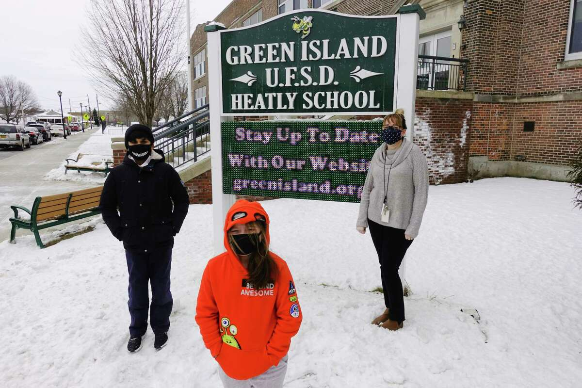Fifth grader Muhammad Khan, 10, left, third grader Maddison Bermudez, 8, center, and art teacher Tanya Harrison, pose for a photo outside the Heatly School on Monday, Feb. 1, 2021, in Green Island, N.Y. Harrison has started a program where students have become pen pals with senior citizens, writing letters and mailing them out. (Paul Buckowski/Times Union)
