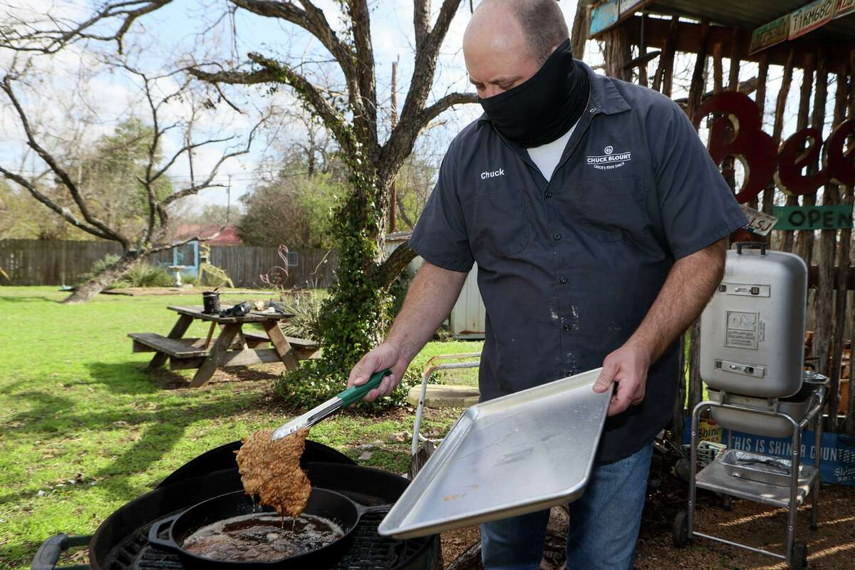 Chuck Blount removes a chicken-fried steak from a cast iron skillet on the grill after cooking it for five minutes per side.