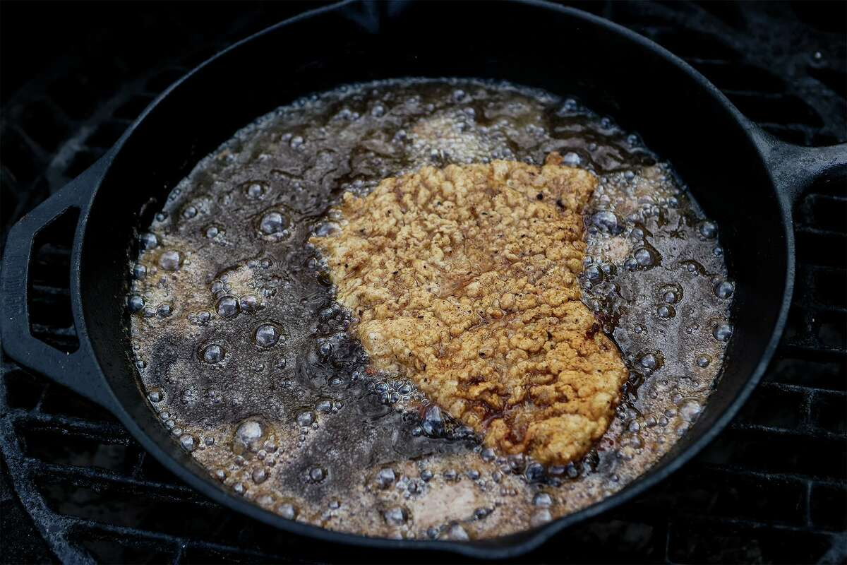 A chicken-fried steak sizzles in a cast iron skillet on the grill.