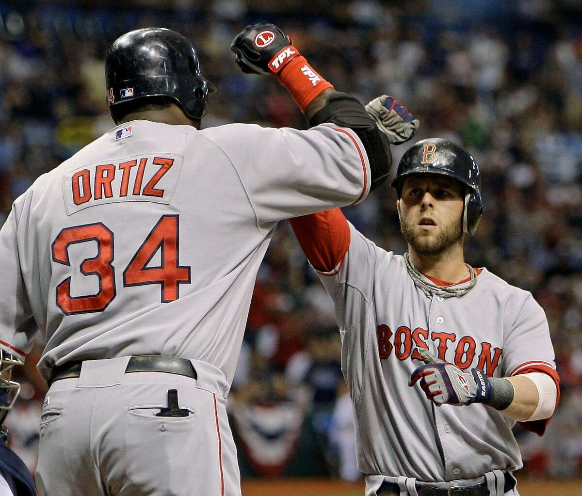Boston Red Sox's Dustin Pedroia, right, is congratulated by teammate David Ortiz after hitting a solo home run against Tampa Bay Rays starting pitcher Matt Garza in the first inning of Game 7 of the American League baseball championship series in St. Petersburg, Fla., Sunday, Oct. 19, 2008. (AP Photo/Chris O'Meara)