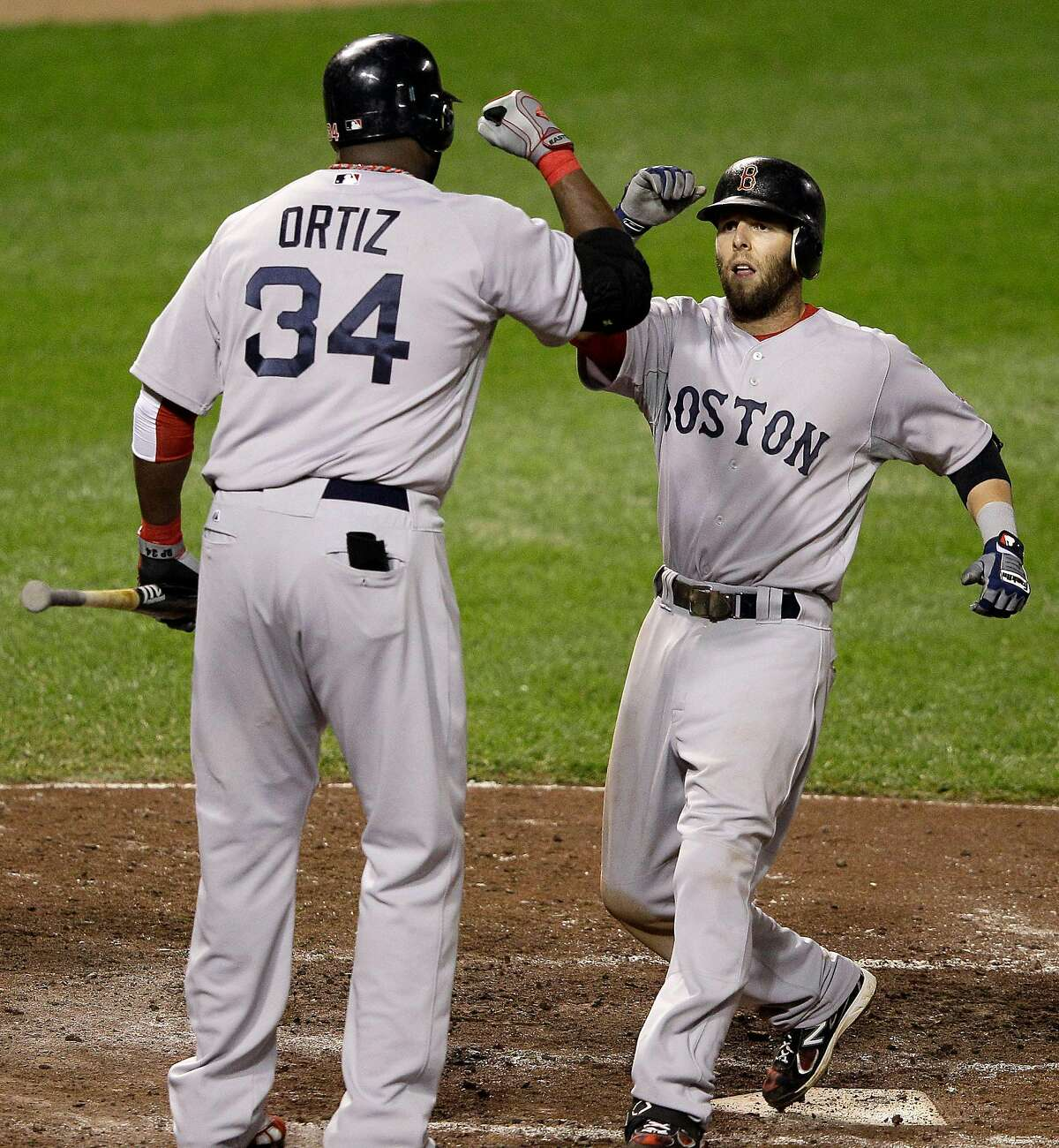 Boston's David Ortiz greets Dustin Pedroia after Pedroia's solo homer against the Orioles on Sept. 28, 2011, in Baltimore.