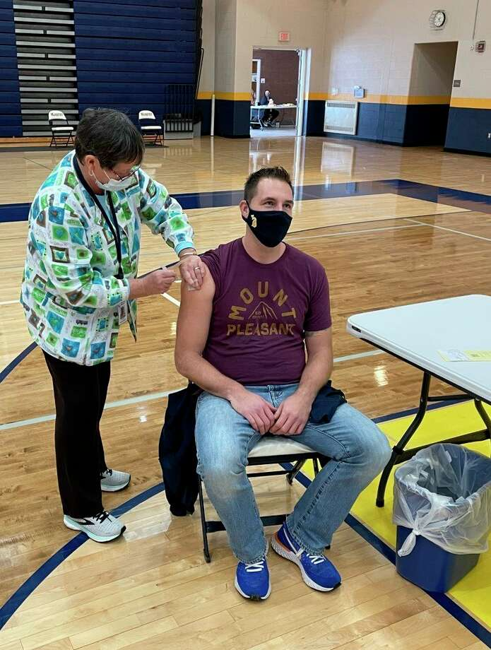 Fourth grade teacher Josh Smith receives a dose of the COVID-19 vaccine at Manistee Middle High School on Friday. Manistee Area Public Schools hosted a clinic in collaboration with District Health Department #10 and vaccinated over 100 district staff members. (Courtesy photo)