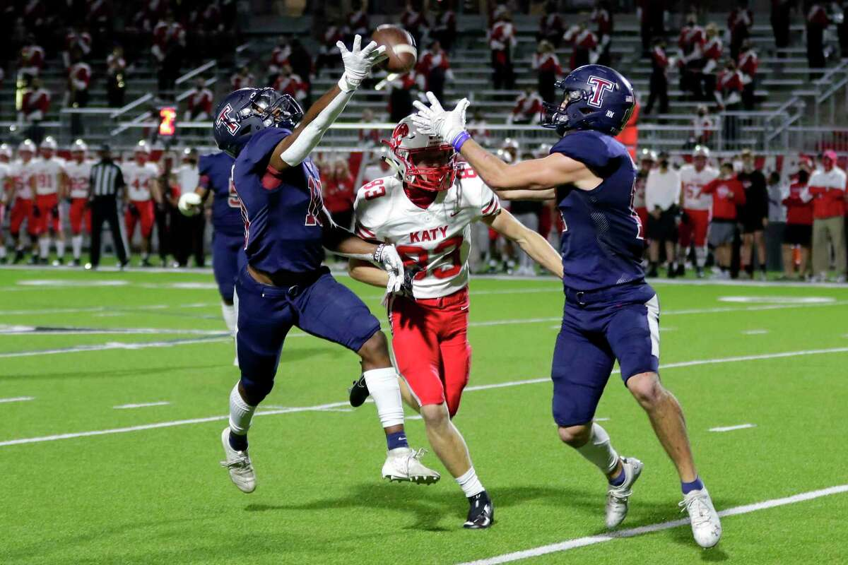 Tompkins defender Koronje Gilbert, left, reaches for the pass intended for Katy's Fuller Shurtz (83) as Colby Huerter, right, pulls in an interception during the first half of a high school football game at Legacy Stadium Thursday, Nov. 5, 2020 in Katy, TX.