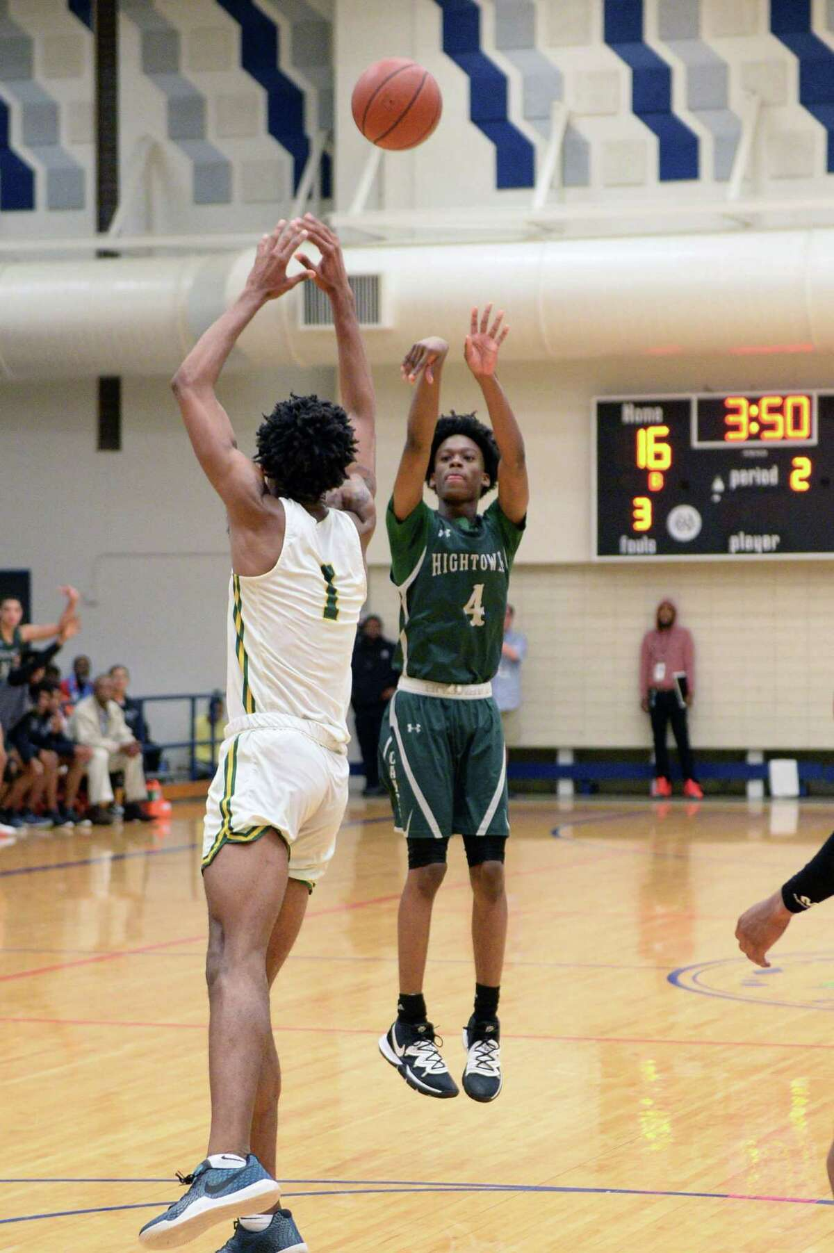 Jacory Chatman (4) of Hightower attempts a 3-point shot over Joshua Farmer (1) of Sharpstown during the first half of a 5A Region III Bi-District playoff game between the Hightower Hurricanes and the Sharpstown Apollos on Monday, February 24, 2020 at Butler Fieldhouse, Houston, TX.