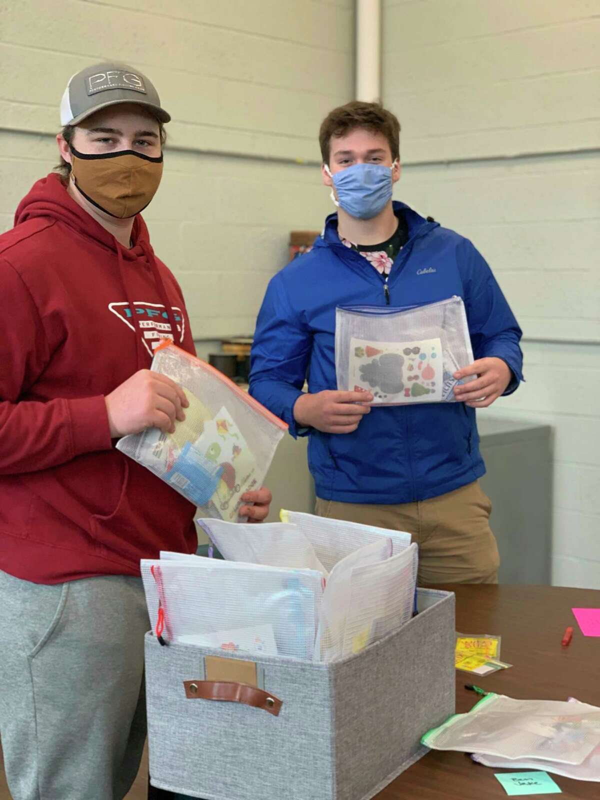 Jake Petrosky (left) and Benjamin Falk of Onekama High School display some completed resource kits on Saturday. (Courtesy photo)