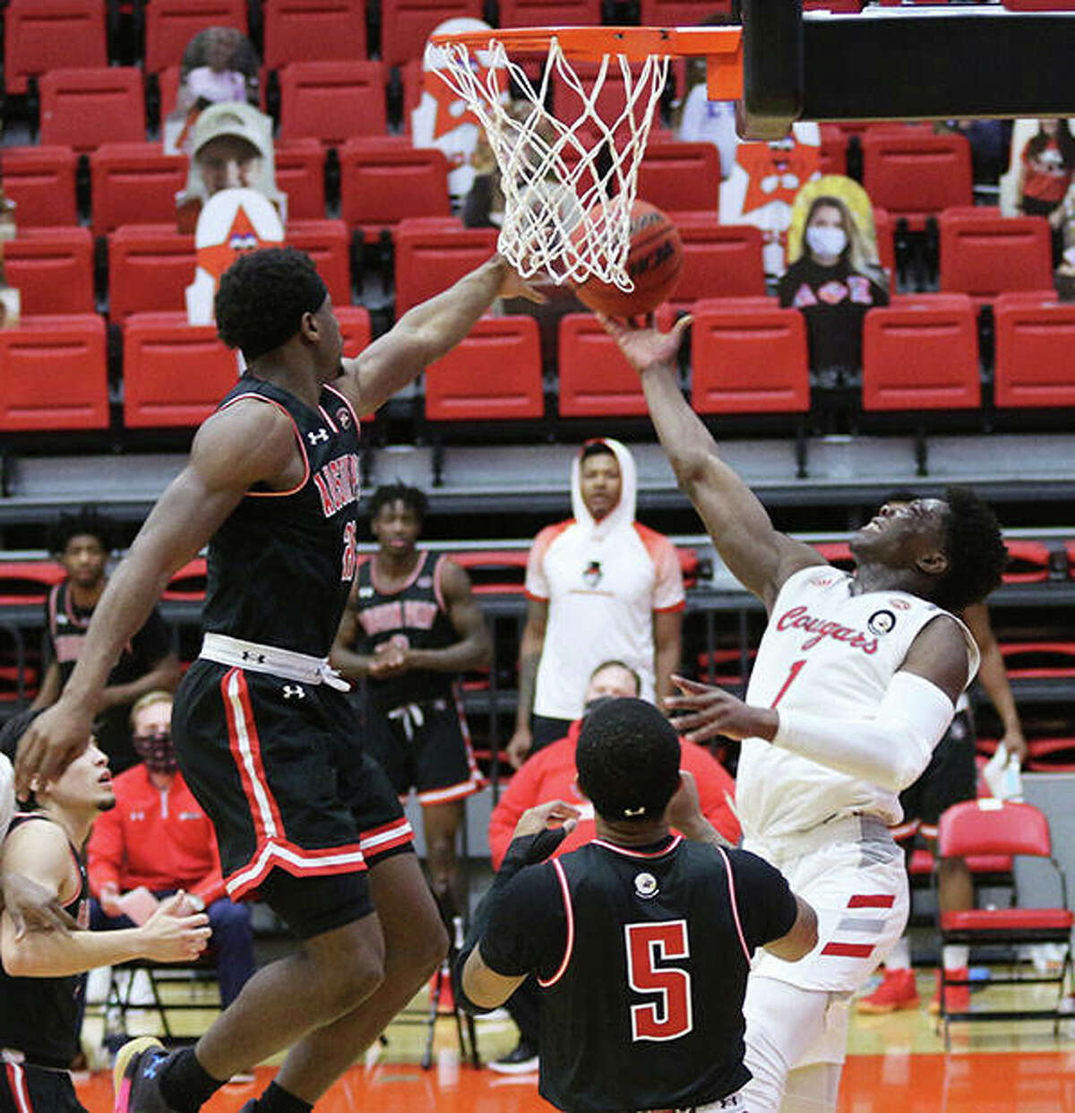 SIUE's Mike Adewunmi (1) extends to get a shot off over Austin Peay's Terry Taylor (left) while Jordyn Adams (5) watches the play Monday in Edwardsville.
