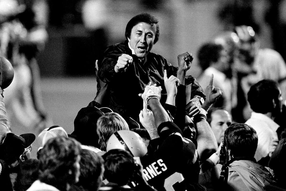 Los Angeles Raiders Coach Tom Flores gestures to members of the as they carry him off the field after their 38-9 victory over the Washington Redskins in Super Bowl XVIII in Tampa, Florida, on Jan. 23, 1984.