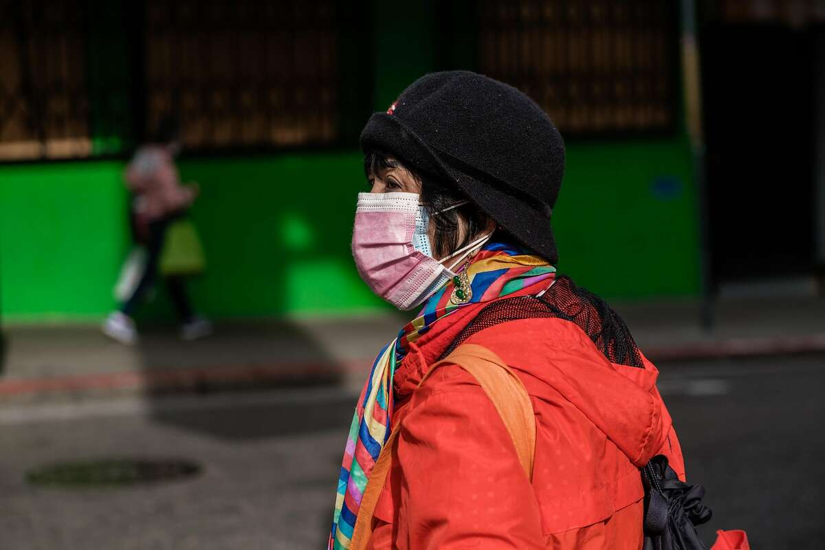 A woman wearing two masks is seen on the street in San Francisco on Thursday, January 21, 2021.