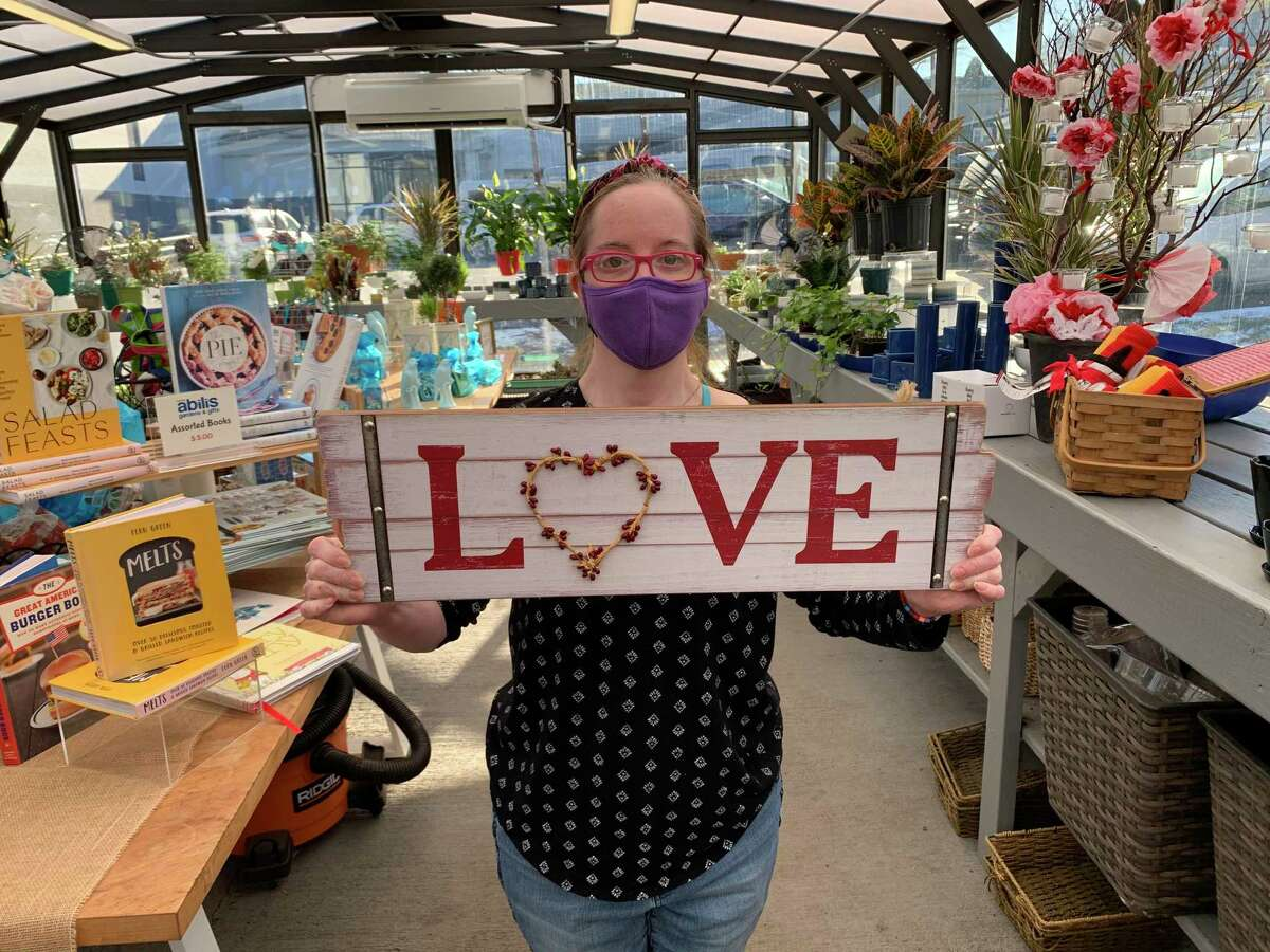 Kristy Kasmarski, an Abilis program participant and part of the employee training program at Abilis Gardens & Gifts, displays an item from the shop.