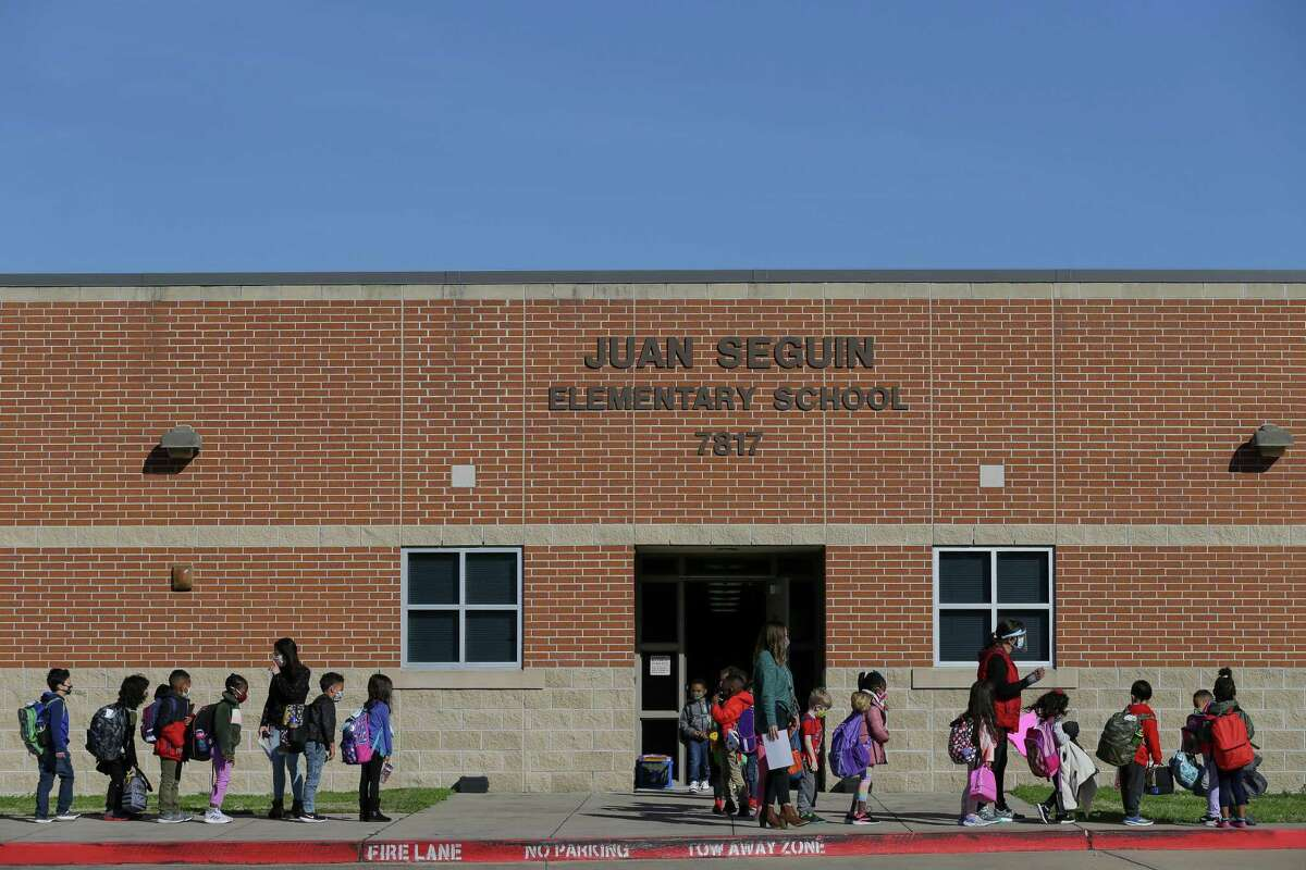 Students at Fort Bend ISD's Seguin Elementary School form a pickup line Monday, the last day of in-person classes scheduled for this week. Although Seguin Elementary reported four active COVID-19 cases as of Monday, fewer than many other campuses that remain open for face-to-face instruction across Greater Houston, administrators in Fort Bend ISD moved classes online amid staffing issues.