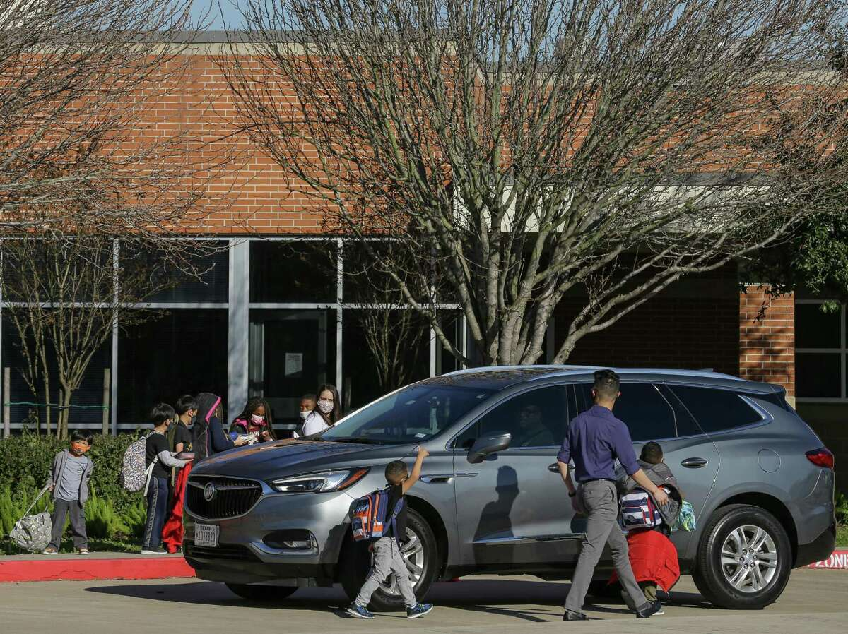 Students at Seguin Elementary School get picked up Monday, the final day of in-person classes this week at the Fort Bend ISD campus.