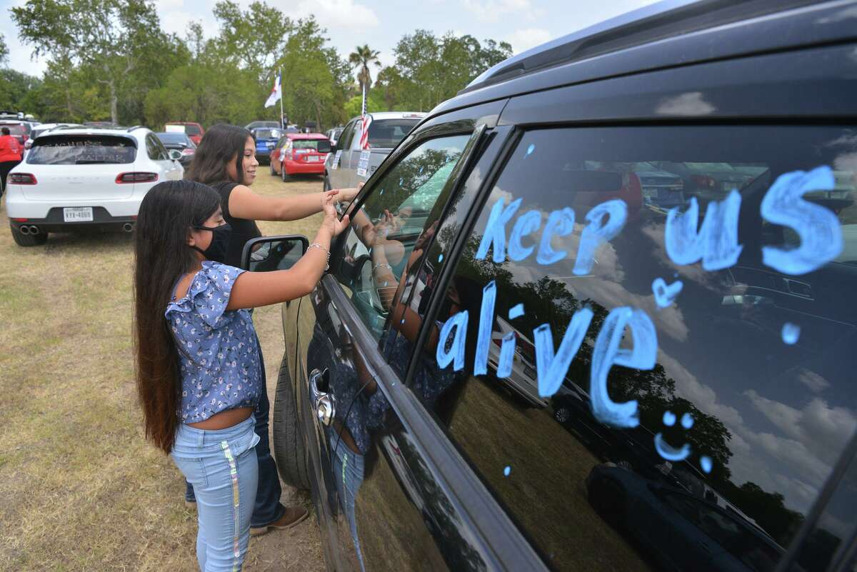 Andrea Solis and her sister Aralin paint their car windows for a parade last July organized by Harlandale ISD teachers urging the state not to impose a deadline to return to in-person learning (it did) and to waive the annual standardized tests, the STAAR, for another year (it didn't).
