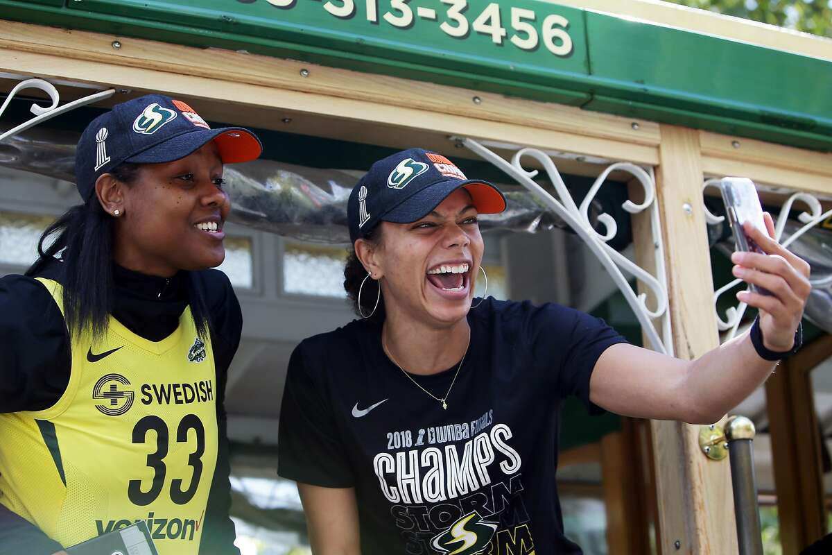 Seattle Storm forward Alysha Clark, right, holds her phone as she and Noelle Quinn, left, take part in a parade to celebrate the Storm winning the 2018 WNBA basketball championship, Sunday, Sept. 16, 2018, in Seattle. (Genna Martin, seattlepi.com)