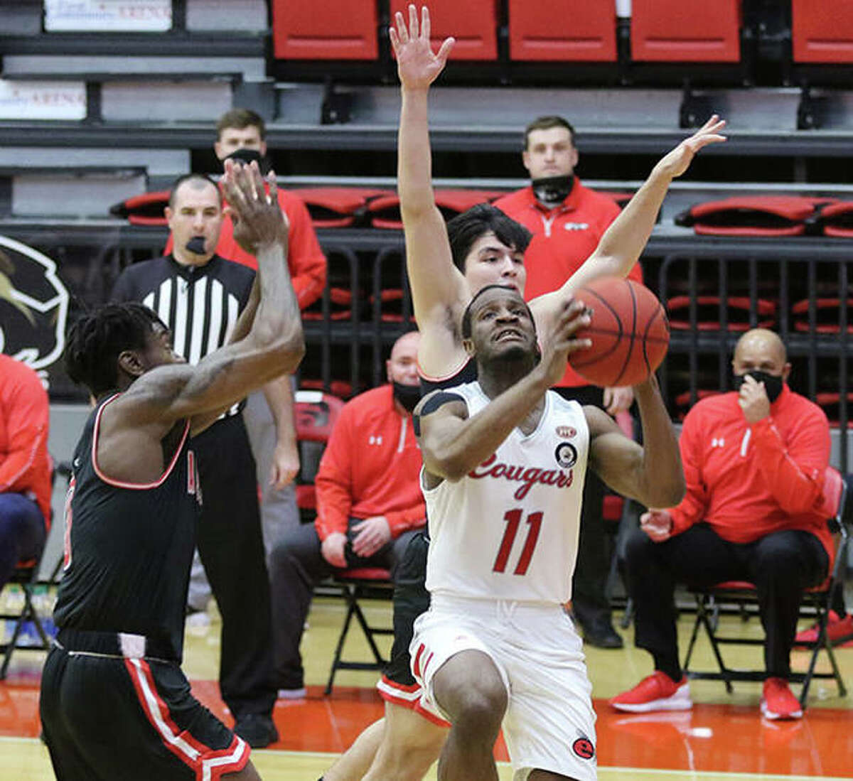 SIUE's Courtney Curtis (11) takes the ball to the rim after beating Austin Peay defenders Monday afternoon in an Ohio Valley Conference men's basketball game at First Community Arena in Edwardsville. It had been 58 days since the Cougars last played at home and they lost to Peay 74-59.
