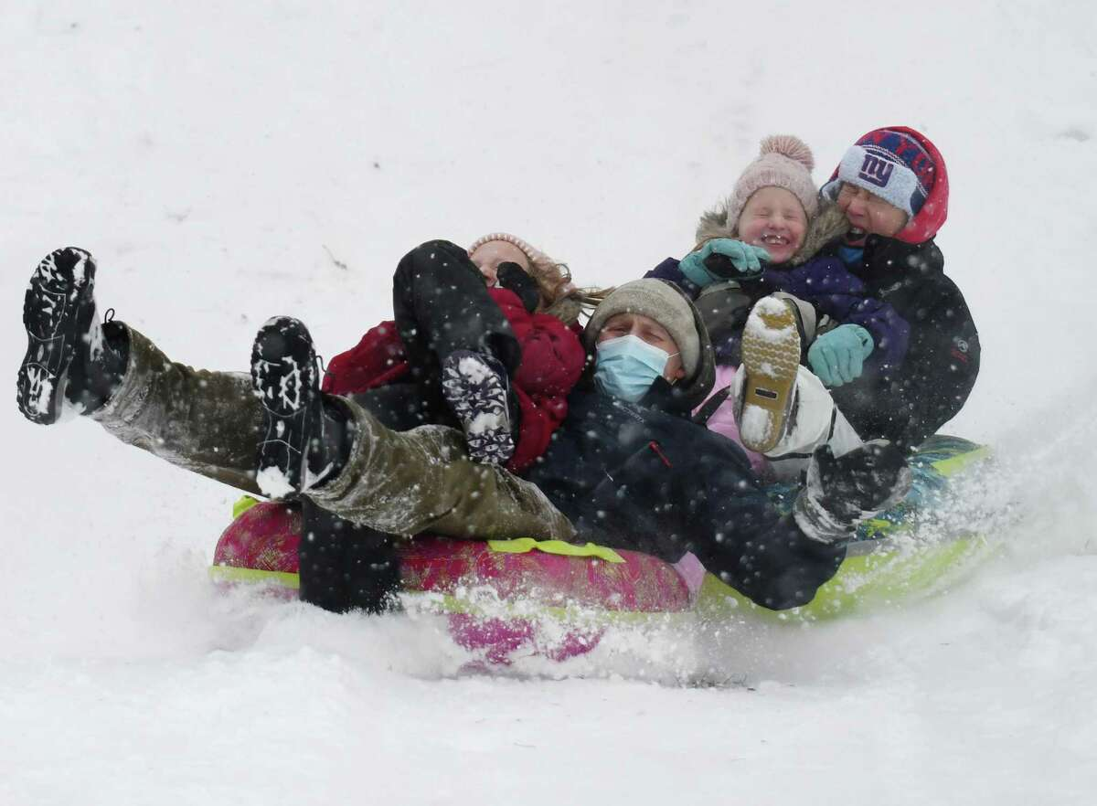 Michael Reid sleds with his daughter, Maggie, 9, as his wife, Jessica, and other daughter, Evie, 6, sled behind while snow falls at North Mianus School in the Riverside section of Greenwich, Conn. Monday, Feb. 1, 2021. The area received consistent light snow starting Sunday evening and continuing throughout the day Monday.