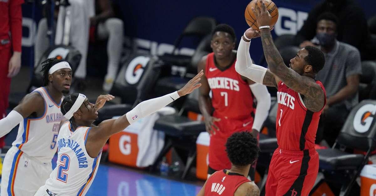 Houston Rockets guard John Wall, right, shoots over Oklahoma City Thunder guard Shai Gilgeous-Alexander (2) in the first half of an NBA basketball game, Monday, Feb. 1, 2021, in Oklahoma City. (AP Photo/Sue Ogrocki)