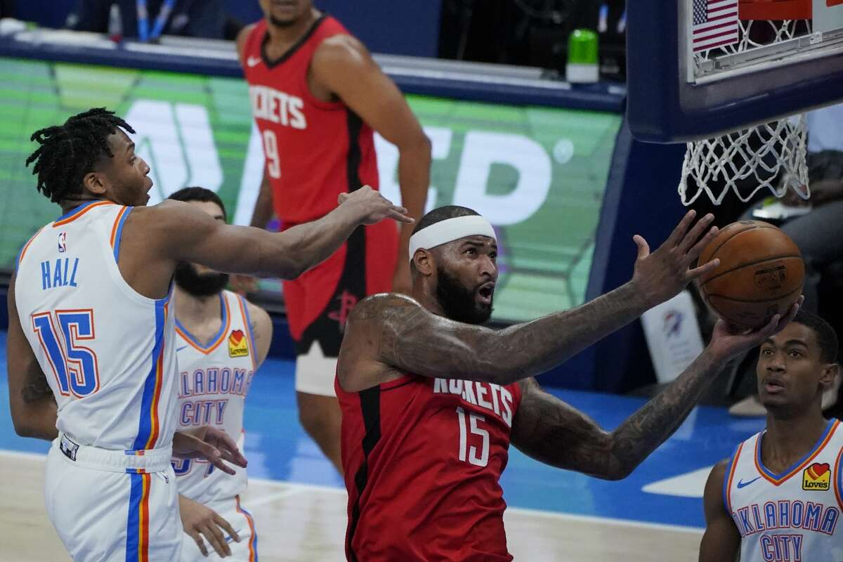 Houston Rockets center DeMarcus Cousins (15) goes to the basket between Oklahoma City Thunder forward Josh Hall, left, and guard Theo Maledon, right, in the second half of an NBA basketball game, Monday, Feb. 1, 2021, in Oklahoma City. (AP Photo/Sue Ogrocki)