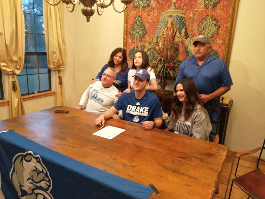 Andrews tight end AJBritten, seated center, signs with the Drake University football program, while surrounded by family during a ceremony Monday at Casabella Bed and Breakfast in Andrews. Photo: Oscar LeRoy
