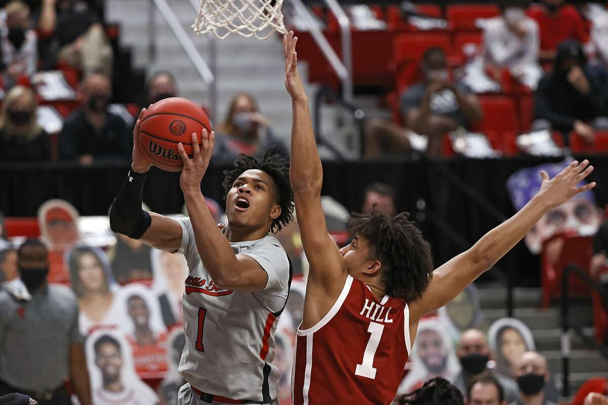 Texas Tech's Terrence Shannon Jr., left, lays up the ball around Oklahoma's Jalen Hill, right, during the second half of an NCAA college basketball game Monday, Feb. 1, 2021, in Lubbock, Texas. (AP Photo/Brad Tollefson)