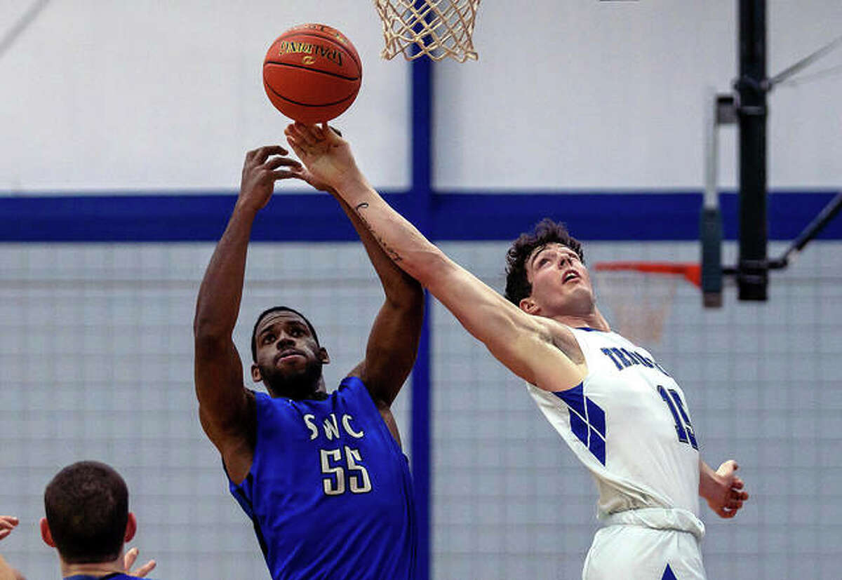 Lewis and Clark Community College forward Zane Short (15), a freshman from Denmark, Wisc., fights for a rebound with SWIC's Adonis Humphreys (55) in LCCC's season opener Monday night at the River Bend Arena.