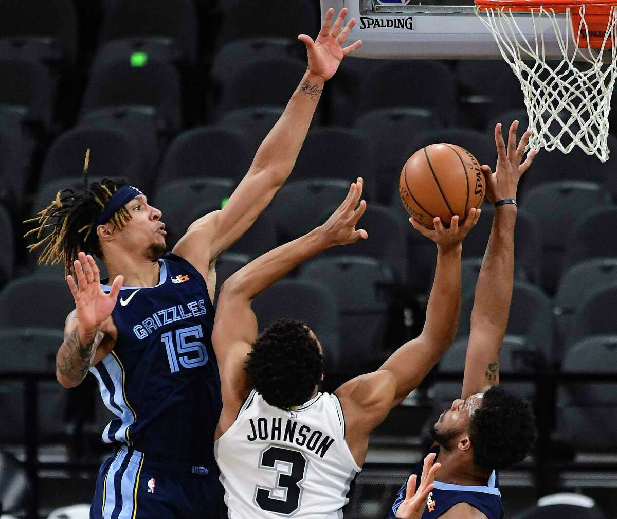 San Antonio Spurs' Keldon Johnson shoots and scores past Memphis Grizzlies Brandon Clarke, left, and Xavier Tillman, right, during first-half NBA action in the AT&T Center on Monday, Feb. 1. 2021.