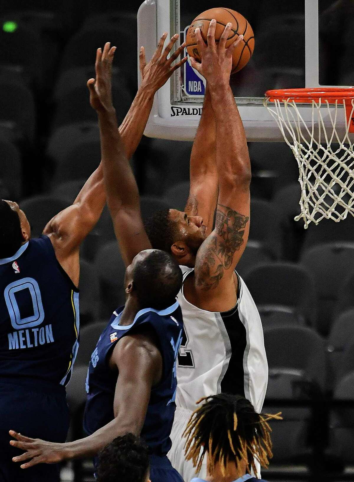 LaMarcus Aldridge of the San Antonio Spurs, in white, dunks against the Memphis Grizzlies during first-half NBA action in the AT&T Center on Monday, Feb. 1. 2021.