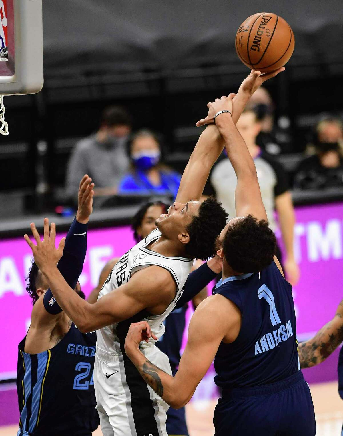 Keldon Johnson of the San Antonio Spurs, middle, shoots and scores as he is fouled by Kyle Anderson (1) of the Memphis Grizzlies during second-half NBA action in the AT&T Center on Monday, Feb. 1. 2021. Johnson scored on the ensuing free throw.