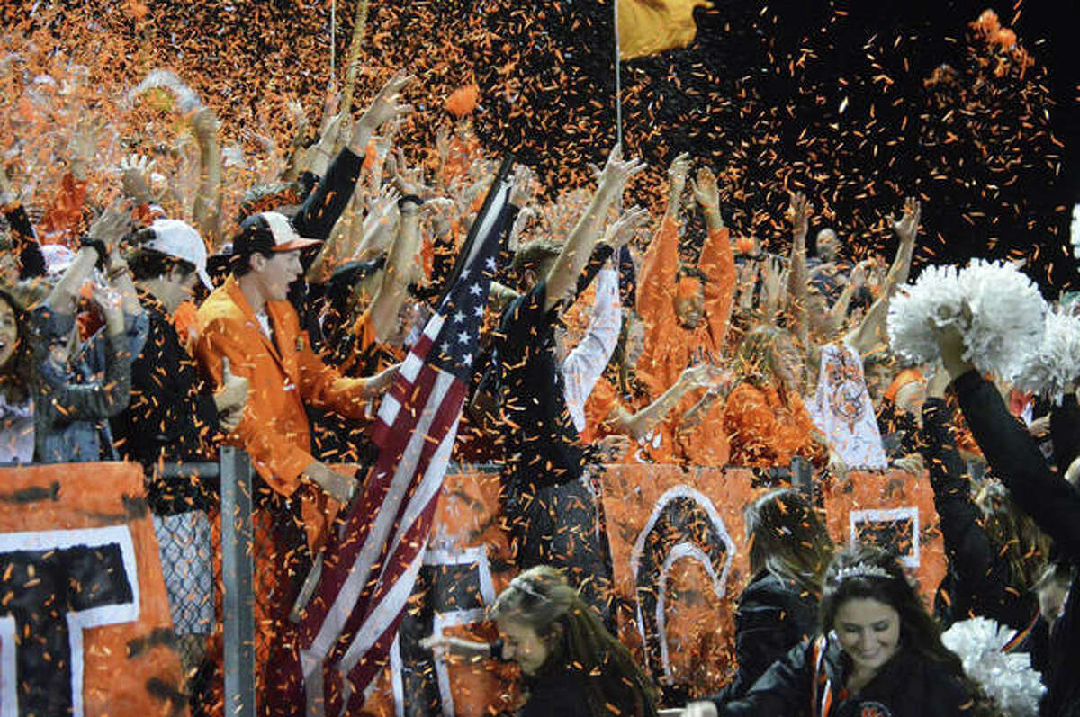 In this file photo from 2018, the Edwardsville High School student section celebrates before the start of the fourth quarter during a home football game. Fans will be limited at sports this season, including boys and girls basketball, boys and girls bowling and boys swimming this winter.