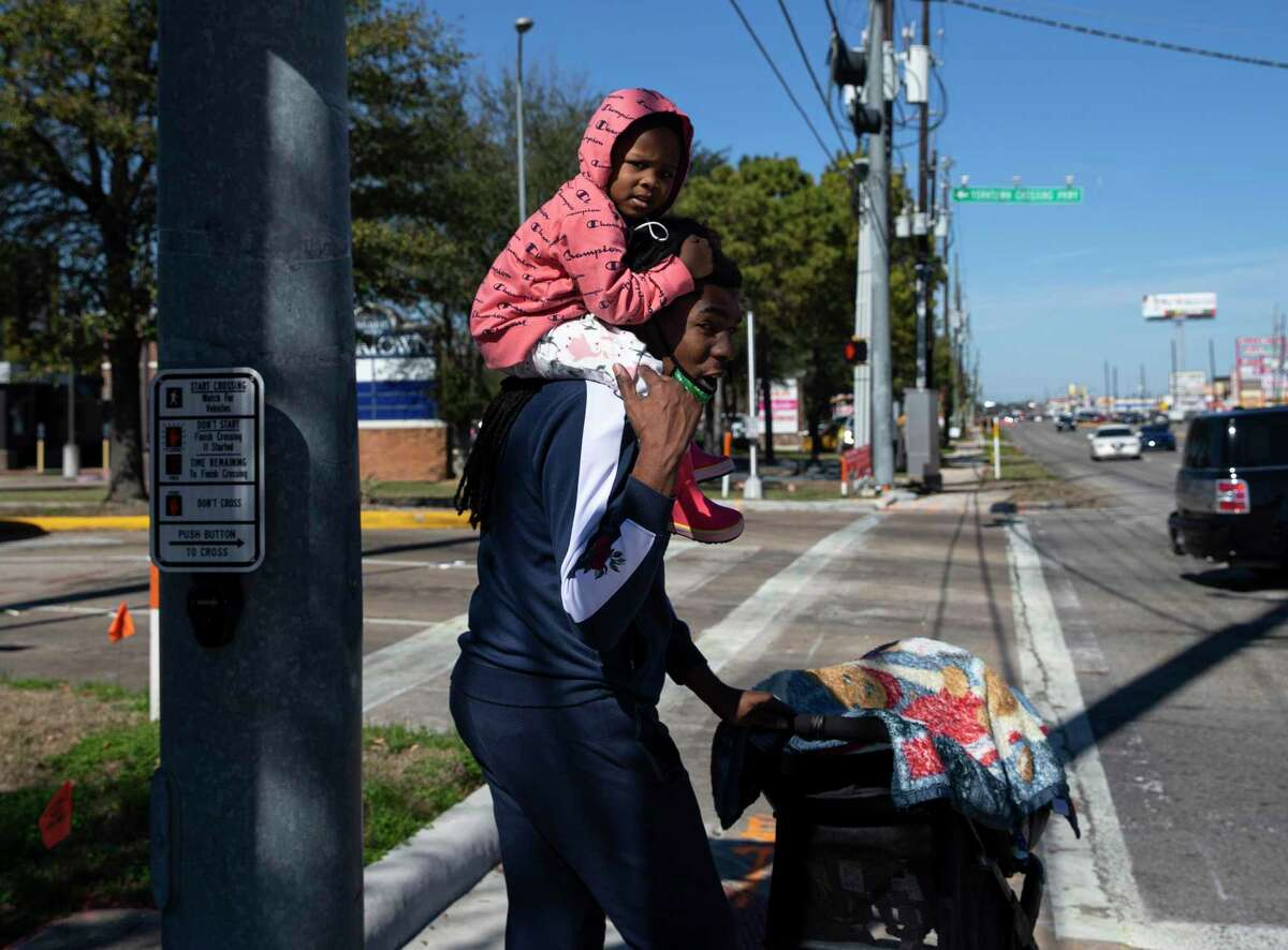 Derron Trent crosses Texas 6 at Yorktown Crossing Parkway on Feb. 1, 2021, in Houston. Trent has been living in this area for almost two years, and before the sidewalks at the intersection were installed said he had to push his older daughter, Naomi, 3, on the road.