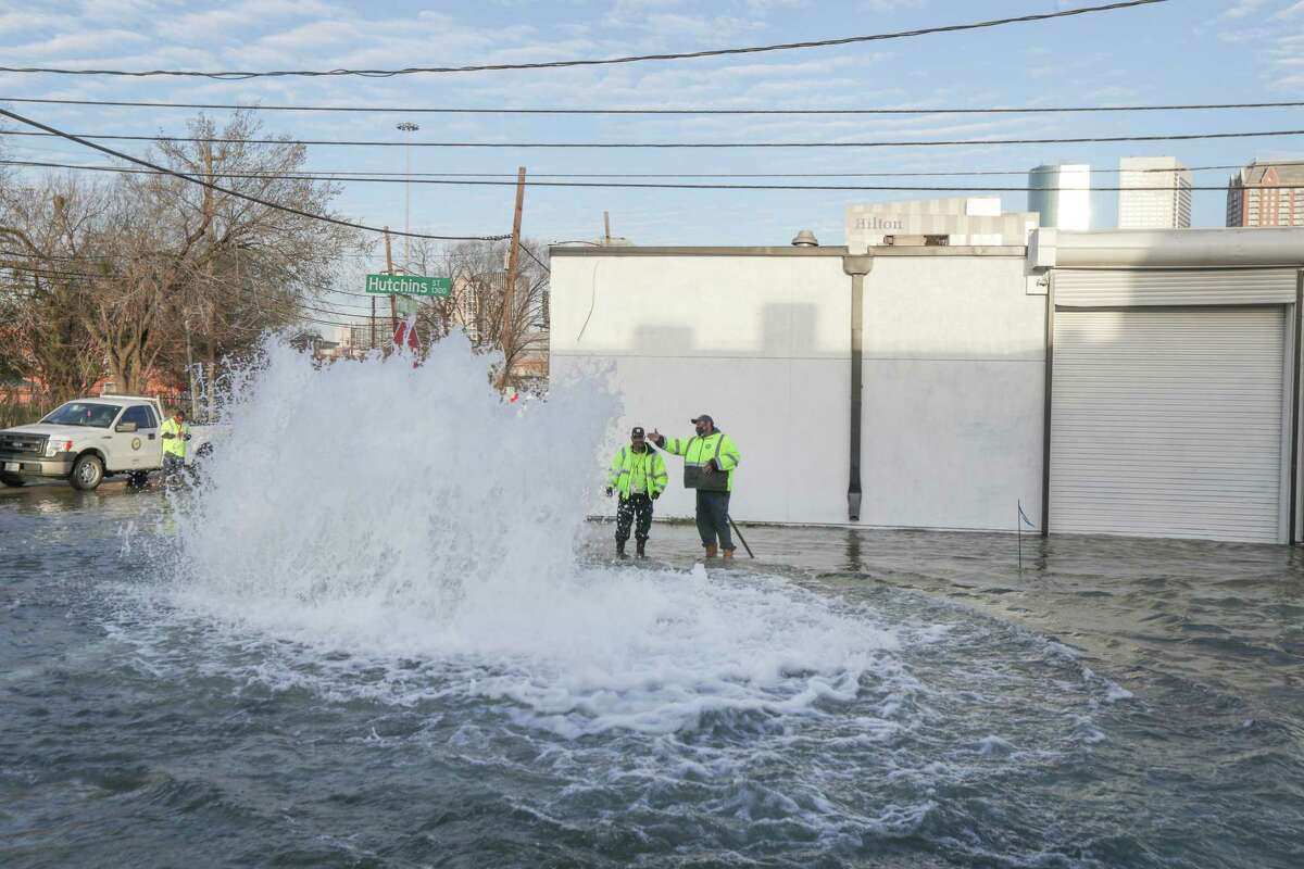 Public Works employees watch a water main break in the EaDo neighborhood at Polk and Hutchins Tuesday, Feb. 2, 2021, in Houston.