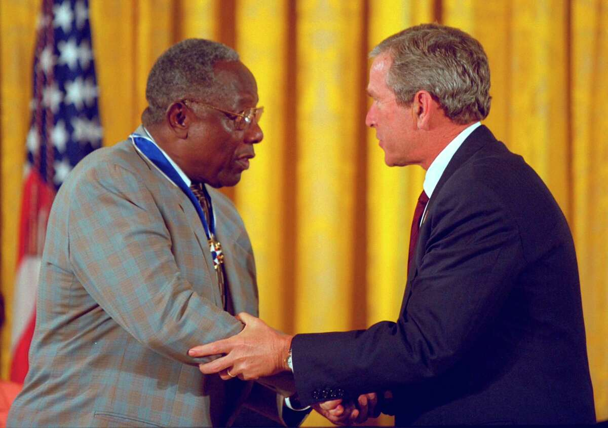 """Former President George W. Bush presents the Presidential Medal of Freedom to baseball legend Henry Aaron during a ceremony at the White House, July 9, 2002. """"The Presidential Medal of Freedom is the highest civil honor our nation can bestow. And we award it today to 12 outstanding individuals,"""" said the president. """"The men and women we honor span the spectrum of achievement. Some are fighters; others are healers; all have left an enduring legacy of hope and courage and achievement."""" (Courtesy photo/Paul Morse/George W. Bush Presidential Library & Museum)"""