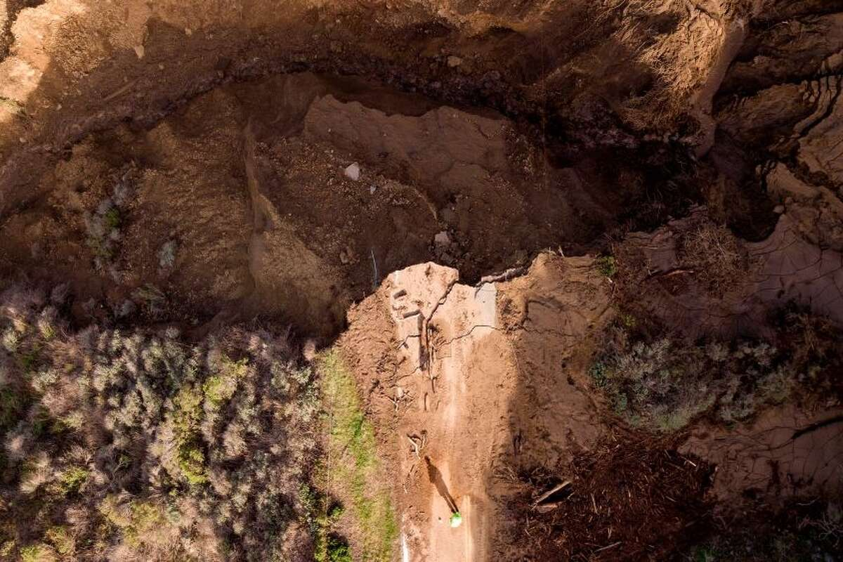 A worker casts a shadow while looking over a section of Highway 1 that collapsed into the Pacific Ocean near Big Sur, California on January 31, 2021. - Heavy rains caused debris flows of trees, boulders and mud that washed out a 150-foot section of the road.
