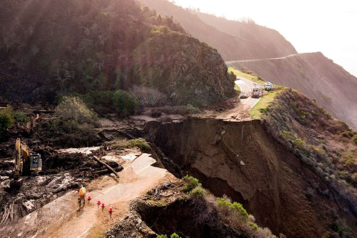 Construction crews work on a section of Highway 1 which collapsed into the Pacific Ocean near Big Sur, California on January 31, 2021. - Heavy rains caused debris flows of trees, boulders and mud that washed out a 150-foot section of the road.
