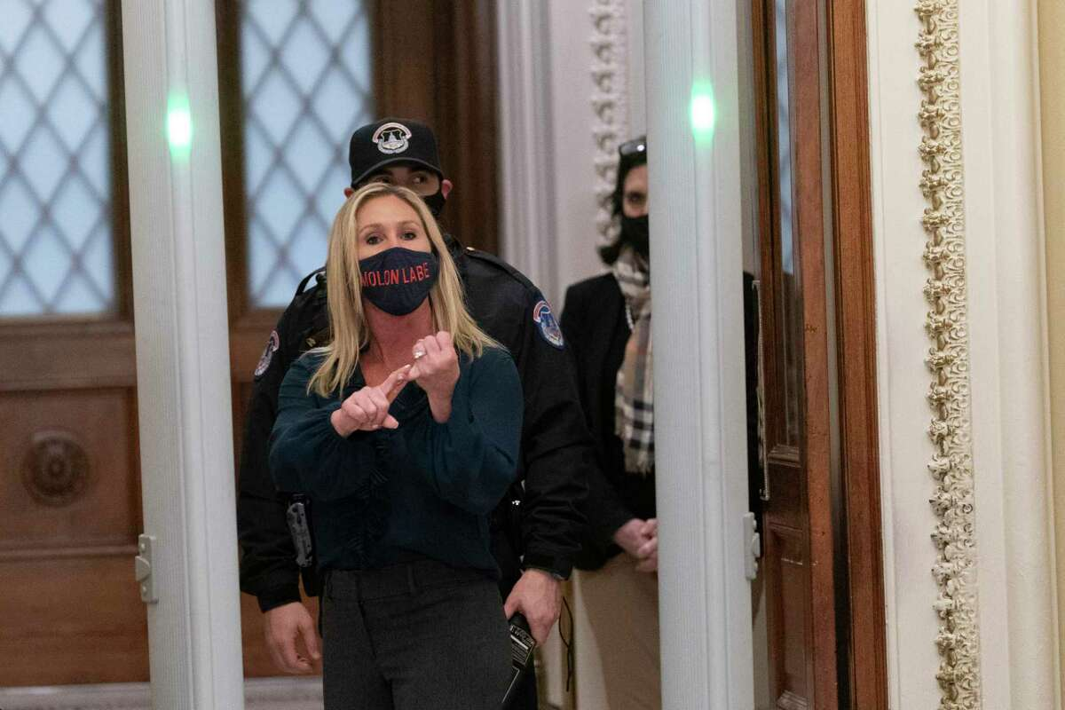 U.S. Rep. Marjorie Taylor Greene, a Georgia Republican, shouts at White House reporter wearing a mask emblazoned with the Greek phrase