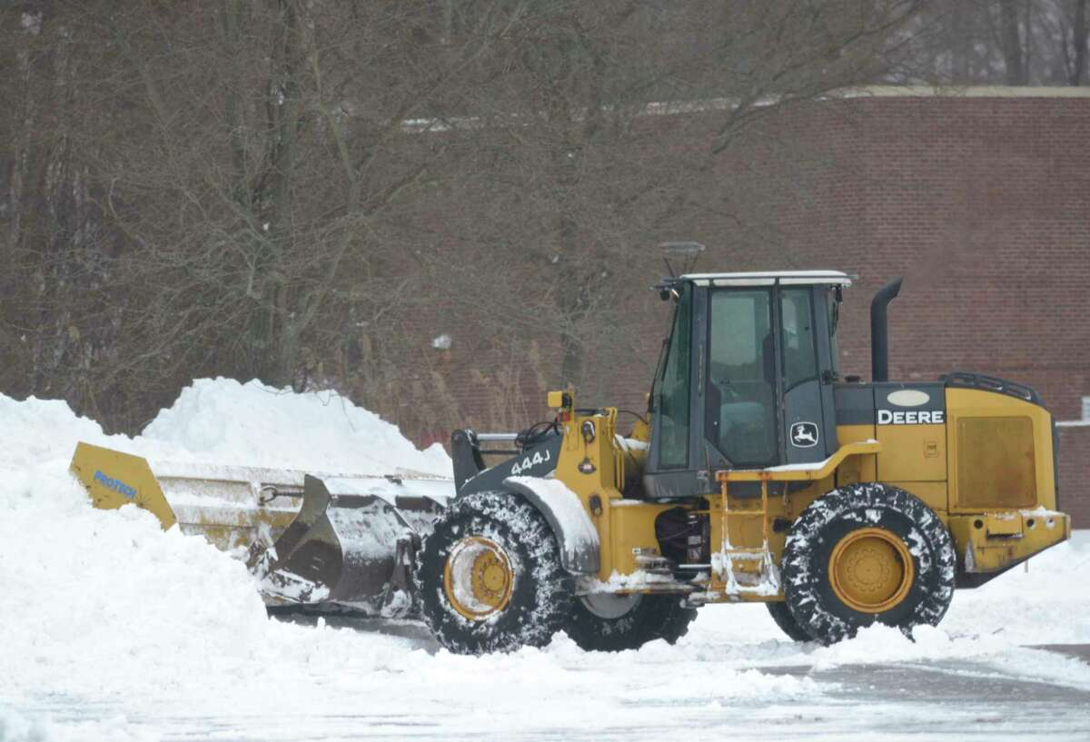 A plow clears snow from the parking lot of Copps Hill Plaza on Tuesday, February 2, 2021, in Ridgefield, Conn.