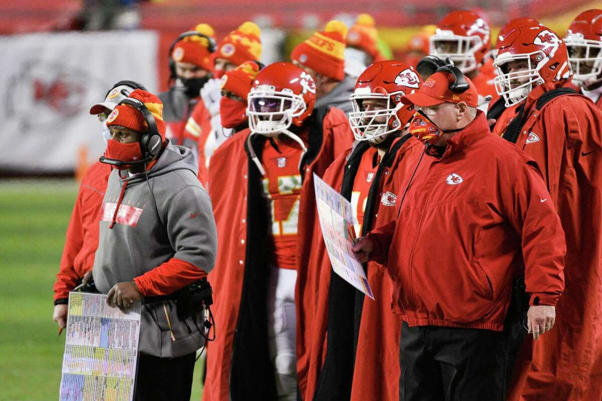 Kansas City Chiefs head coach Andy Reid (right) and offensive coordinator Eric Bieniemy (far left, with play sheet) watch from the sidelines during the first half of the NFL AFC championship football game against the Buffalo Bills, Sunday, Jan. 24, 2021, in Kansas City, Mo. (AP Photo/Reed Hoffmann)