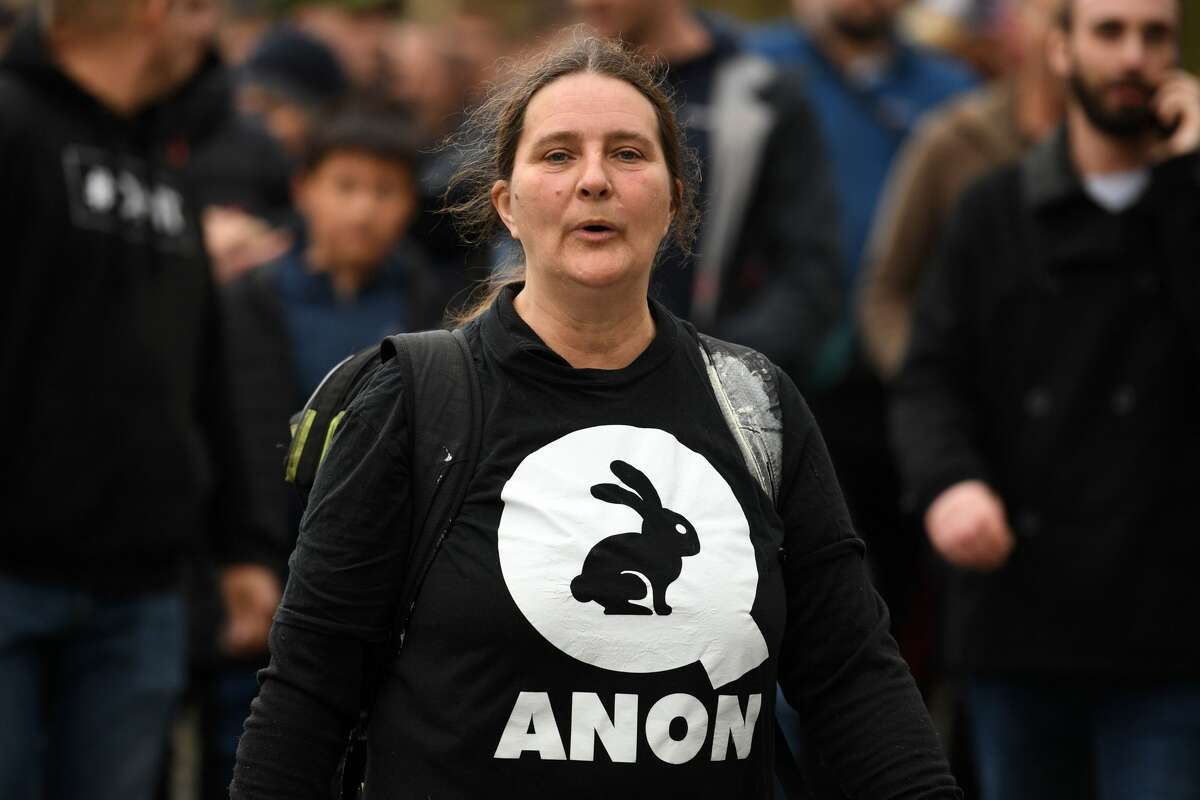 Q goes international: A woman wearing a QAnon graphic on her shirt attends a gathering of protesters outside St. George's Hall during an anti-vaccine rally in Liverpool on Nov. 14, 2020.