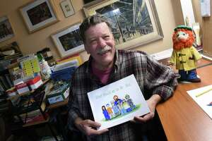 Cartoonist Roger Straub in his studio at his home in Higganum with a mock up of his latest book in a series with the character, Mac O'Moodus, on October 5, 2020. At right is a Mac O'Moodus doll.