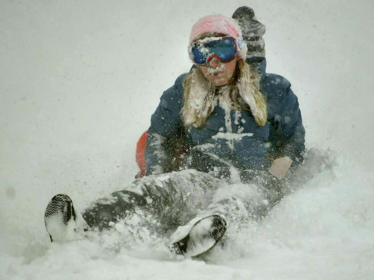 Friends Lucy Hurlbut, left, and Carly Guarino, both of Fairfield, sled in near white out conditions at Sturges Park in Fairfield, Conn. on Monday, February 1, 2021.