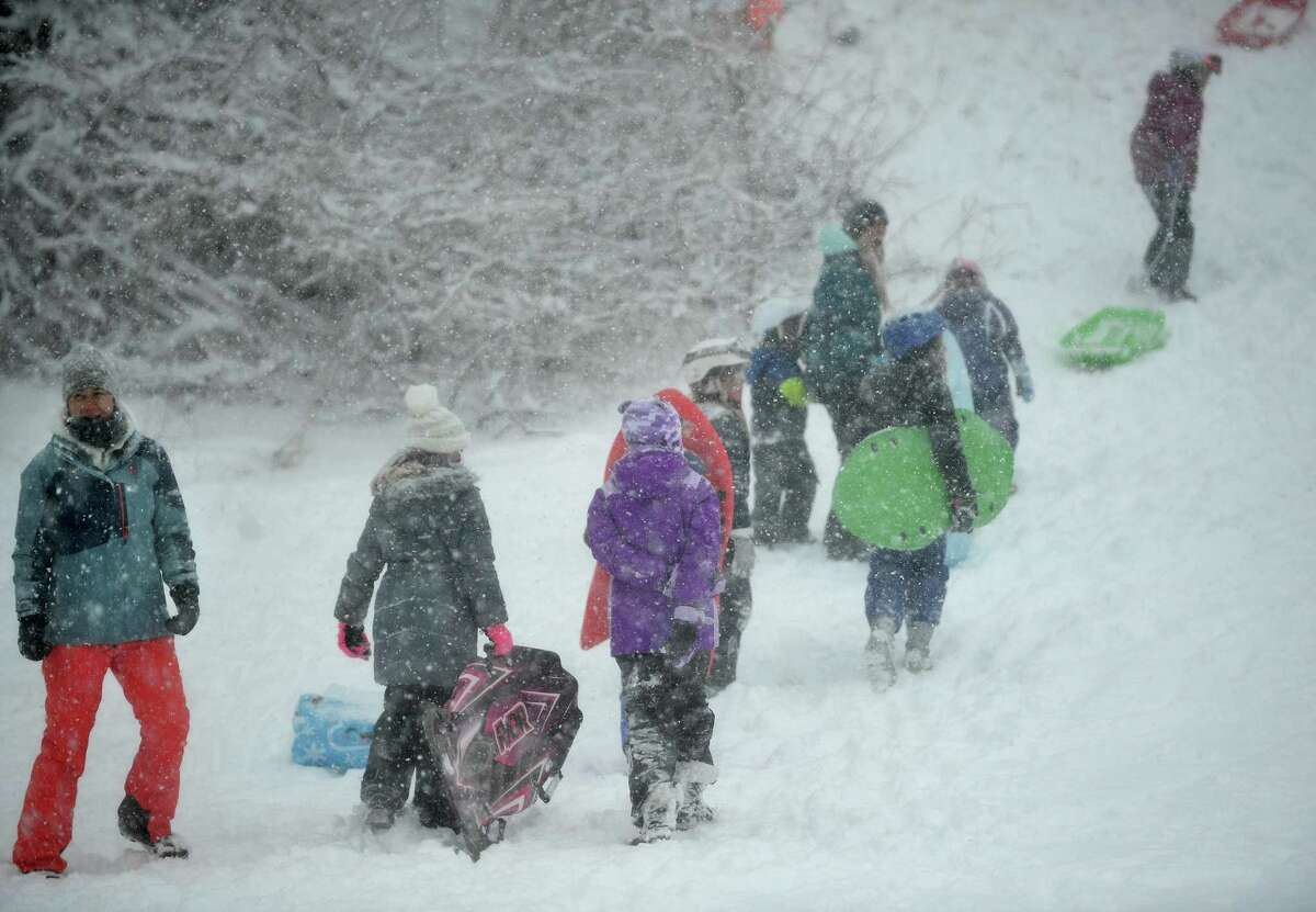 Sled riders make their way to the top of the hill in near white out conditions at Sturges Park in Fairfield, Conn. on Monday, February 1, 2021.
