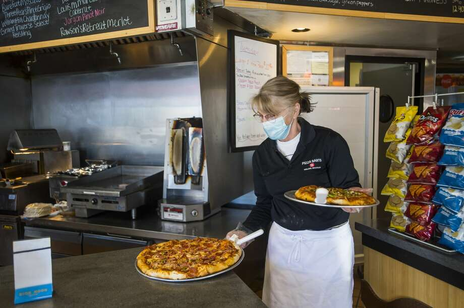 Dawn Rugenstein carries two pizzas to a table during the lunch rush Tuesday, Feb. 2, 2021 at Pizza Sam's in downtown Midland. (Katy Kildee/kkildee@mdn.net) Photo: (Katy Kildee/kkildee@mdn.net)