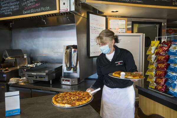 Dawn Rugenstein carries two pizzas to a table during the lunch rush Tuesday, Feb. 2, 2021 at Pizza Sam's in downtown Midland. (Katy Kildee/kkildee@mdn.net)