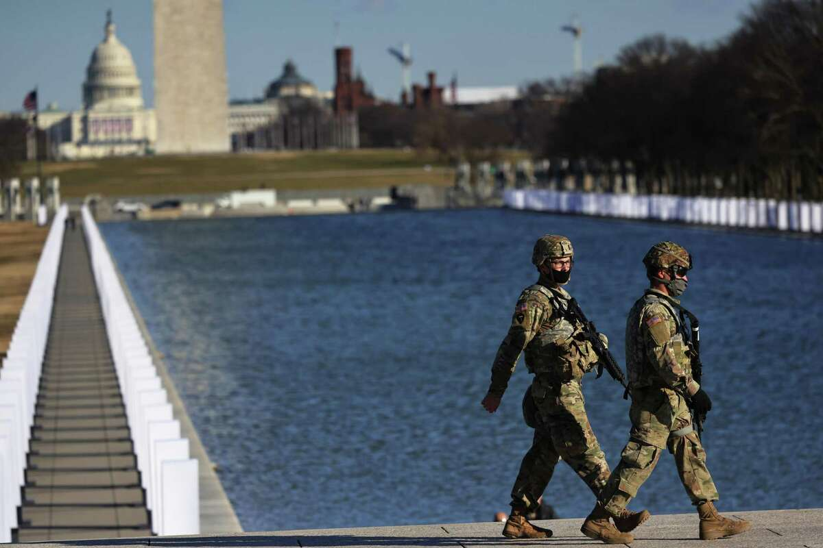 National Guard soldiers patrol the grounds of the Lincoln Memorial ahead of President-elect Joe Biden and Vice President-elect Kamala Harris attending a national memorial for victims of the coronavirus pandemic on Jan. 19, the eve of the presidential inauguration. (Photo by Michael M. Santiago/Getty Images)