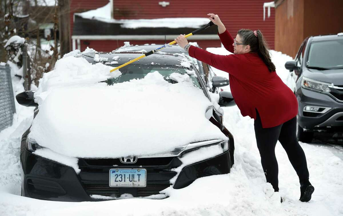 Kathy Radin clears snow from her nephew's car in Ansonia on February 2, 2021.