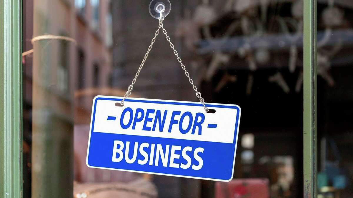 An open for business sign welcomes passing customers. (Photo courtesy of Getty Images)