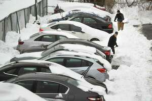 Residents dig out their snowed in cars on Canal Street in Shelton, Conn. on Tuesday, February 2, 2021.