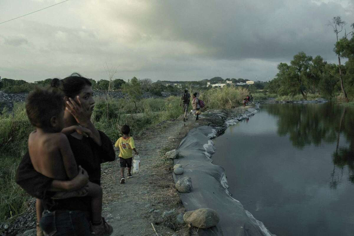 Migrants walk along a river in Tapachula, Chiapas state, Mexico, on Friday, Jan. 29, 2021. U.S. President Joe Biden and Mexican PresidentAndres Manuel Lopez Obrador agreed to work together to stem the flow of irregular migration to their countries, the White House said. Photographer: Nicolo Filippo Rosso/Bloomberg