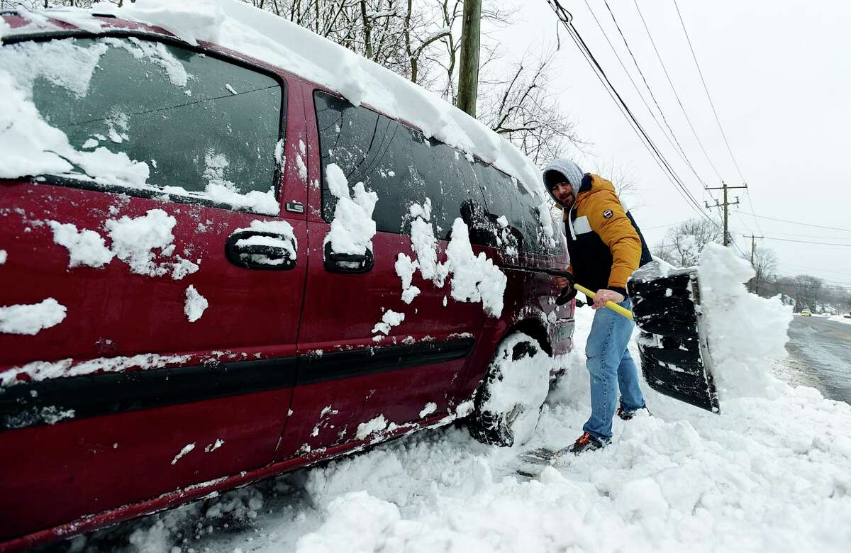 Norwalk residents Tom Derario cleans around his vehicle on Warde Street after the snowstorm Tuesday, February 2, 2021, in Norwalk, Conn